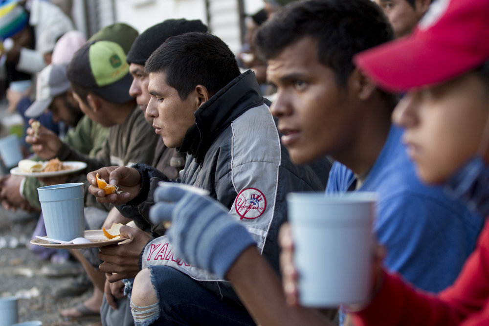 Central American migrant men eat dinner in front of the El Barretal shelter on Saturday, December 1, 2018 in the Desarrollo Urbanoejido Matamoros neighborhood of Tijuana, Mexico. Photo By: Jose Lopez / Corsair Contributor