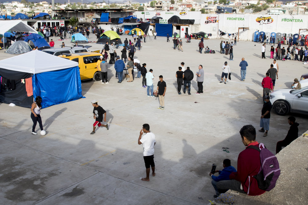 Migrant teenagers play soccer at El Barretal, a migrant shelter set up in Tijuana, Mexico, Saturday, Dec. 1, 2018. These migrants are some of the first to make the move from the previous shelter at the Benito Juarez sports complex to El Barretal due to rainfall causing flooding at Benito Juarez. Although flooding made living conditions poor, some people stayed at Benito Juarez because of it's proximity to the office for asylum seeking applications. Photo By: Zane Meyer-Thornton/ Corsair Contributor