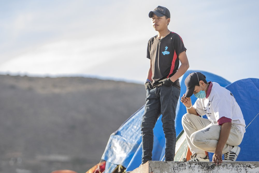 Young teenage male members of the Central American migrant caravan stand on the edge of a balcony overlooking other members of the caravan arrive at the El Barretal nightclub, turned into a temporary shelter in Tijuana, Mexico, Saturday, Dec. 1, 2018. Photo By: Daniel Bowyer / Corsair Contributor