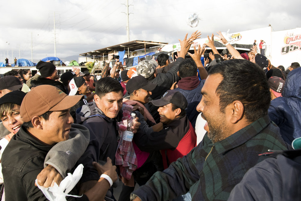 Central American migrant caravan members temporarily living at the El Barretal shelter struggle to grab bags filled with goods being thrown from a pickup truck in Tijuana, Mexico, Saturday, Dec. 1, 2018. El Barretal was a former concert venue and night club that has been temporarily turned into a migrant shelter. Photo By: Zane Meyer-Thornton/ Corsair Contributor