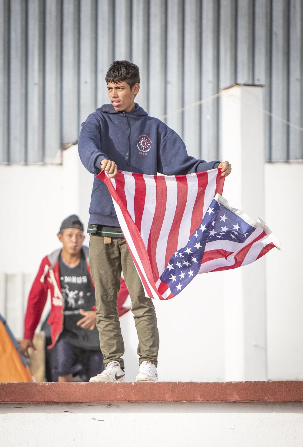 A young male, part of the migrant caravan, holds up an American Flag, while other members of the caravan arrive at the El Barretal nightclub, turned into a temporary shelter in Tijuana, Mexico, Saturday, Dec. 1, 2018. Photo By: Daniel Bowyer / Corsair Contributor