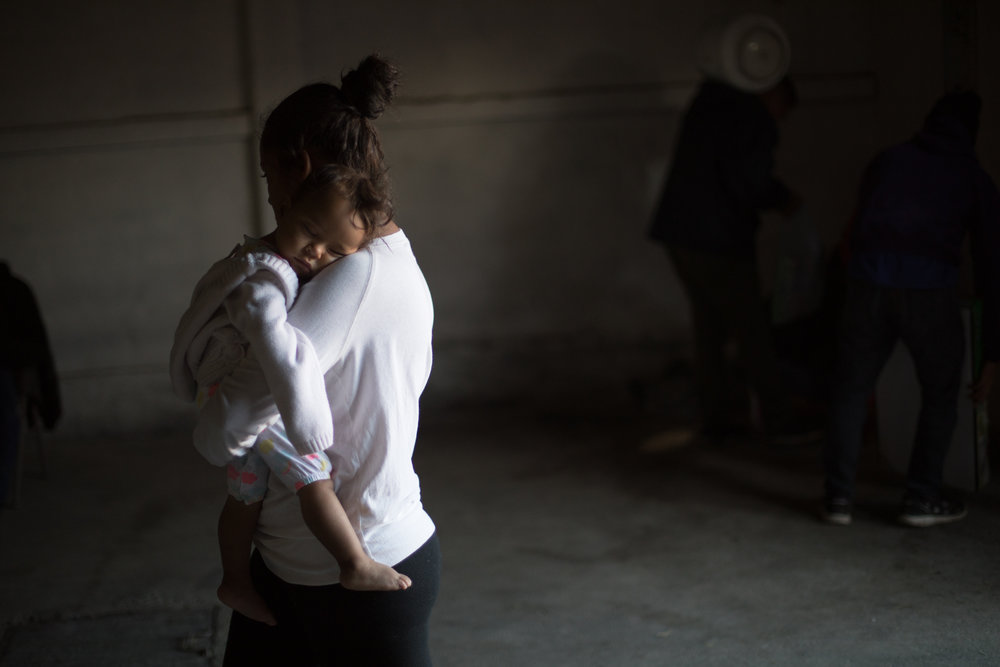 A mother carries her sleeping child into the women and children's shelter at El Barretal in Tijuana, Mexico, Sunday, Dec. 2, 2018. The specially designated structure for women and children contains a former bar that is now a temporary dispensary of diapers, baby formula and personal hygiene items. Health workers and volunteers man the facility wearing medical masks as many refugees have become ill after the former shelter was flooded by rain. Asylum seekers previously housed at Benito Juarez sports complex have been moved on Friday, Nov. 30, 2018, due to flooding from rainfall. The new camp location, El Barretal, is a former concert venue that has been repurposed into an impromptu shelter. Photo By: Zin Chiang / Corsair Contributor