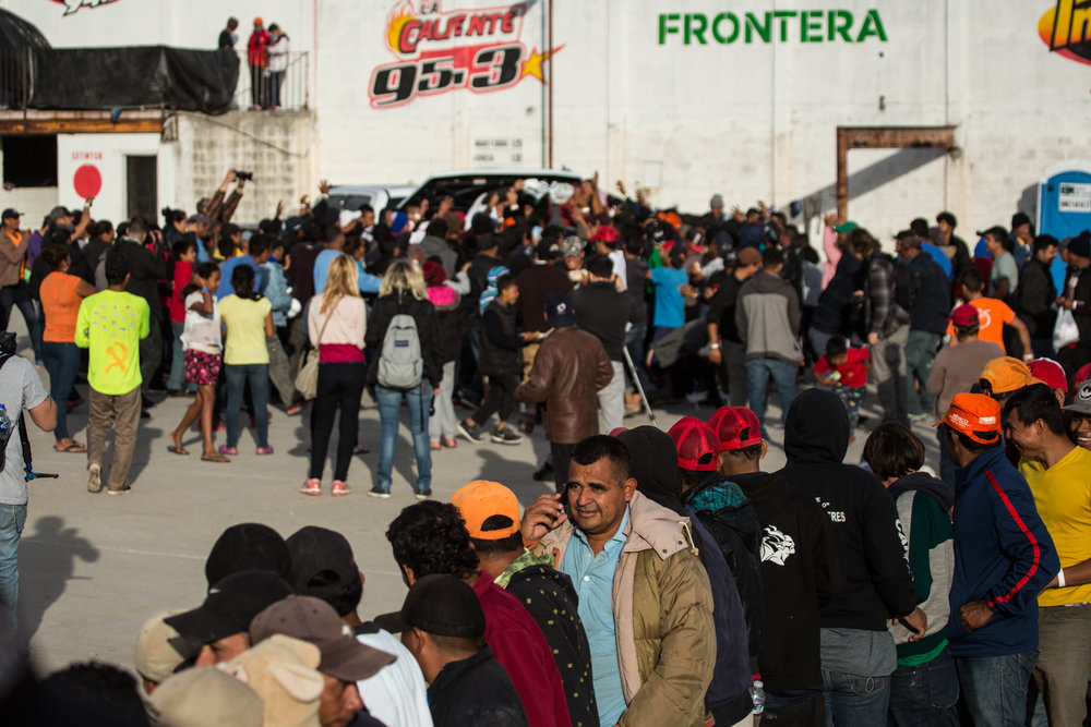 Displaced Hondurans wait in line to receive hot meals prepared by non-government aid groups at Barretal in the Desarollo Urbanojito Matoros district of Tijuana, Mexico on Dec 1, 2018. In the background, others attempt to catch care packages containing clothing being thrown from a pickup truck. Asylum seekers previously housed at Benito Juarez have been moved on November 30, 2018 due to flooding from rainfall. The new camp location, Barretal, is a former concert venue that has been repurposed into an impromptu shelter. Photo By: Zin Chiang / Corsair Contributor