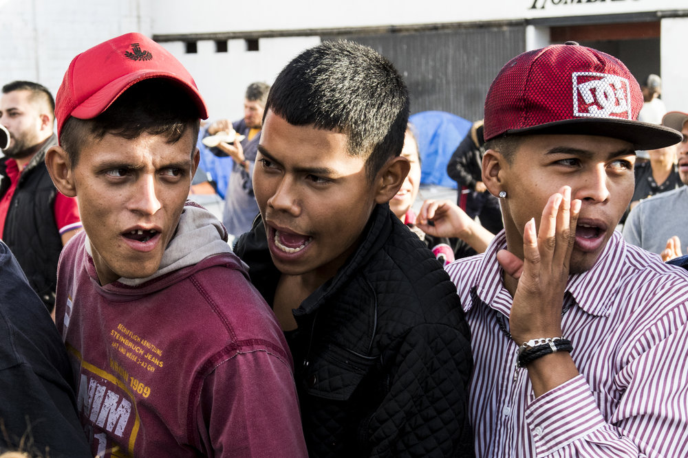 Three migrant teenage males shout to draw attention to people cutting a line for supplies at the El Barretal shelter, a former concert venue turned migrant shelter in Tijuana, Mexico, Saturday, Dec. 1, 2018. Photo By: Zane Meyer-Thornton/ Corsair Contributor
