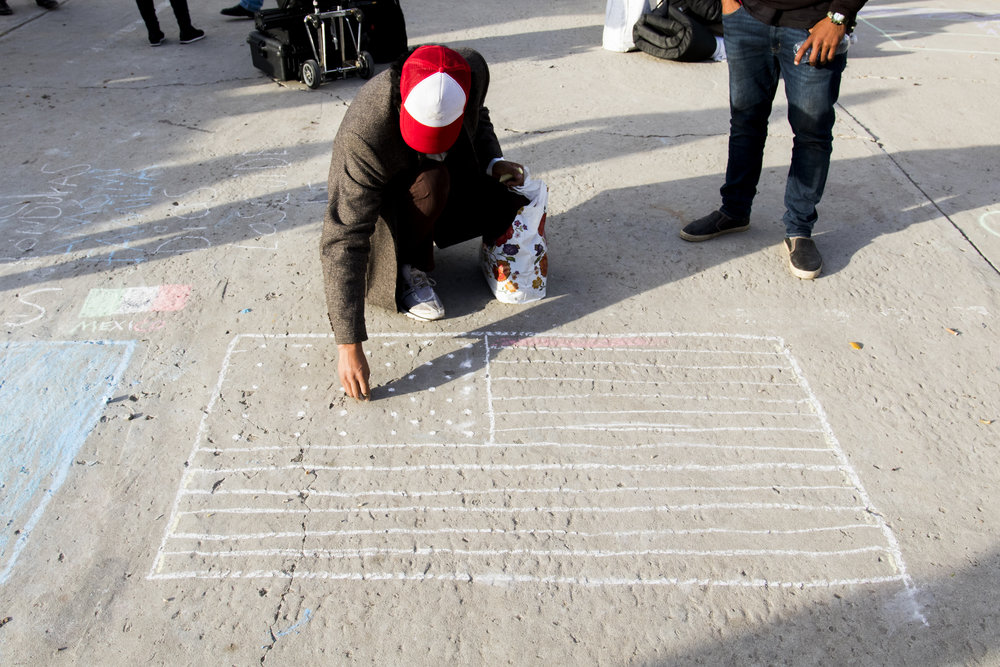 Christian, a migrant male, uses chalk to draw an American Flag on the ground of the El Barretal shelter  in Tijuana, Mexico, Saturday, Dec. 1, 2018. Photo By: Zane Meyer-Thornton/ Corsair Contributor