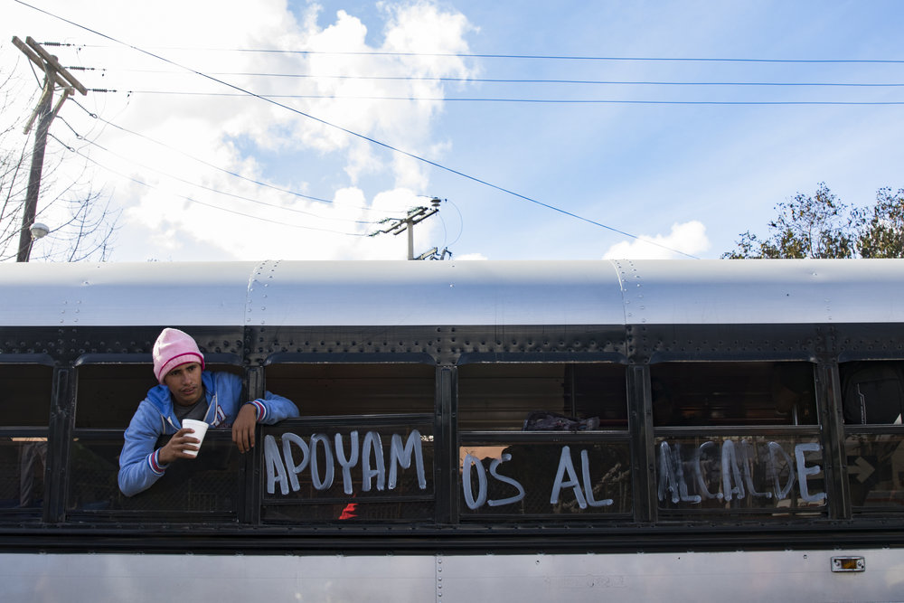"Jose Miguel waits for a bus to transport him from a migrant shelter located at the Benito Juarez Sports Complex to a new location in El Barretal on December 1, 2018 in Tijuana, Mexico. The bus has a sign that reads ""Apoyam os al alcalde"" which means We Support the Mayor. Photo By: Zane Meyer-Thornton / Corsair Contributor"