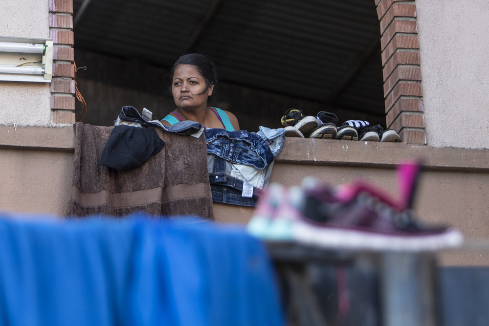 A woman part of the Central American migrant caravan takes shelter in the family ward of the El Barretal nightclub, turned into a temporary shelter  in Tijuana, Mexico, Saturday, Dec. 1, 2018. Photo By: Daniel Bowyer / Corsair Contributor