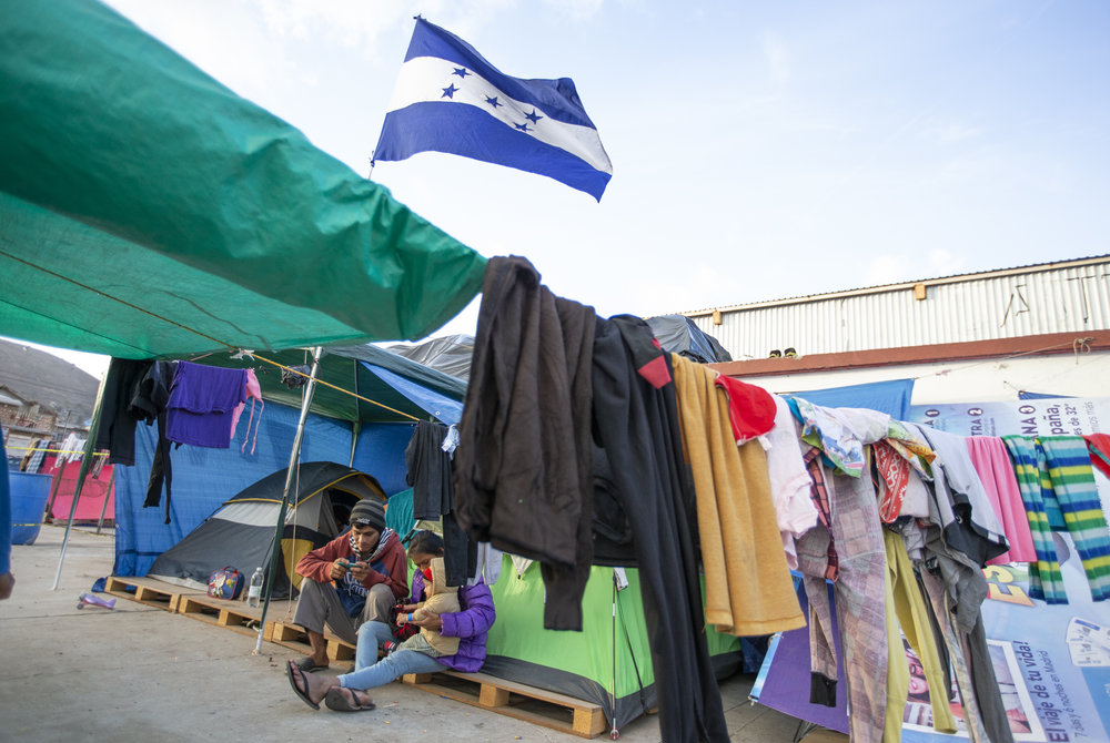 A family part of the Central American migrant caravan take shelter in tents under the National flag of Honduras at the El Barretal nightclub, turned into a temporary shelter in, Mariano Matamoros, Tijuana, B.C., Mexico. December 1st, 2018. Photo By: Daniel Bowyer / Corsair Contributor