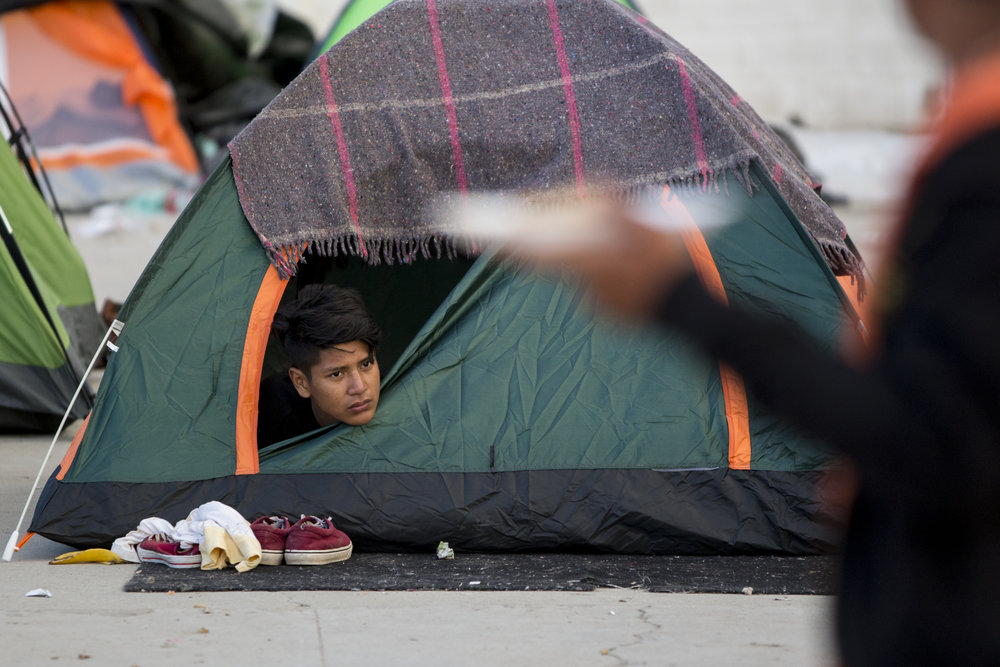 A young Central American migrant peeks out from his tent looking at the long line of people waiting to be fed at the El Barretal shelter on Saturday, December 1, 2018 in the Desarrollo Urbanoejido Matamoros neighborhood of Tijuana, Mexico. Photo By: Jose Lopez / Corsair Contributor