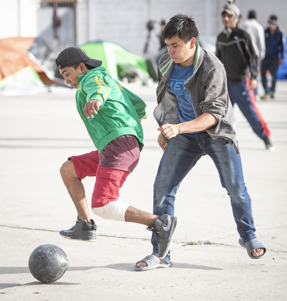 Young male migrant caravan members playing soccer at the El Barretal nightclub turned into a temporary shelter in Tijuana, Mexico, Saturday, Dec. 1, 2018. Photo By: Daniel Bowyer / Corsair Contributor