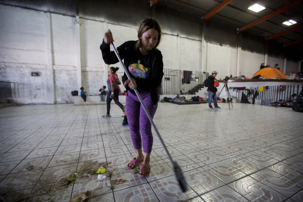 Joanna Caseres, 20, from Honduras, helps clean up the new shelter space, El Barretal, in preparation to receive evacuated Central American migrants on Saturday, December 1, 2018 in the Desarrollo Urbanoejido Matamoros neighborhood of Tijuana, Mexico.The new location, El Barretal, is a space that was previously a club and concert venue, which is now being repurposed as a shelter for the Central American migrants being evacuated from the flooded Benito Juarez Sports Complex. Photo By: Jose Lopez / Corsair Contributor