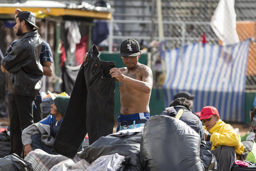 A migrant who has not yet evacuated the flooded space attempts to recover personal items at the Benito Juarez sports complex on Saturday, Dece. 1, 2018, in Tijuana, Mexico. Photo By: Jose Lopez / Corsair Contributor