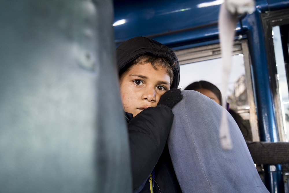 A young child waits for his bus to leave a migrant shelter hosted at the Benito Juarez sports complex in Tijuana, Mexico, Saturday, Dec. 1, 2018. The bus is headed towards El Barretal, a former concert venue in Tijuana, Mexico that is now being used as a migrant shelter because heavy rainfall flooded the sport complex and made the living conditions very unsanitary. Photo By: Zane Meyer-Thornton/ Corsair Contributor