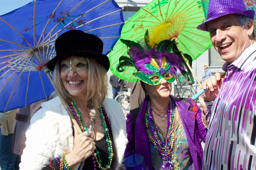 Friends gather at the pre-parade party prior to the start of the 17th annual Venice beach Mardi Gras, in Los Angeles, California, on Feb 23, 2019. (From left to right) Gretchen Neville, Kelly Breaux, and Damian Boudreaux are all from Louisiana. Photo by Danica Creahan.