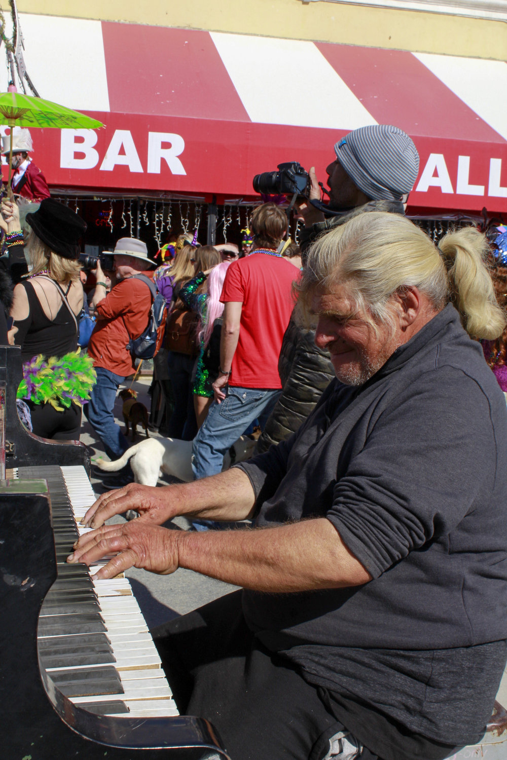 """Nathan Pino plays his piano on the Venice Beach boardwalk as the Venice Beach Mardi Gras parade floods past him on Feb 23, 2019 in Los Angeles, California. Nathan plays his Piano on the boardwalk every day, and the influx of people and instruments to play along to seemed to brighten his day. """"It's a nice birthday present,"""" Says Nathan. Photo by Danica Creahan."""