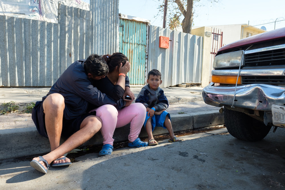 A man comforts his wife outside of Benito Juarez Sports Complex in Tijuana, Mexico on November 16, 2018. (Photo by Jayrol San Jose)
