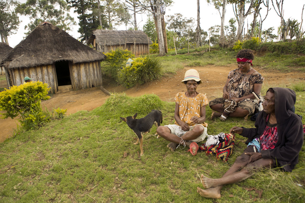 Three women make bilums in a village on Gun-Beroma Road, Simbu Province, Papua New Guinea.