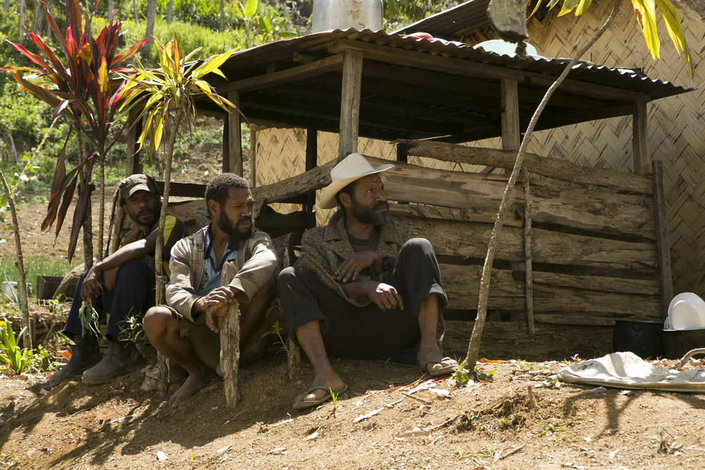 Bulb onion farmer Max Soa (right) and farm workers take a cigarette break. Maramun village, Simbu Province, Papua New Guinea.