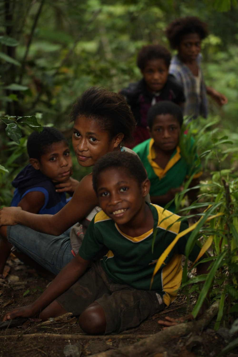Ohu village children run ahead, arranging themselves in various tableaux in the forest, to surprise the hiking party from Binatang Research Centre, Ohu Conservation Area, near Madang, Papua New Guinea.  Published in  Cosmos Magazine December-January issue