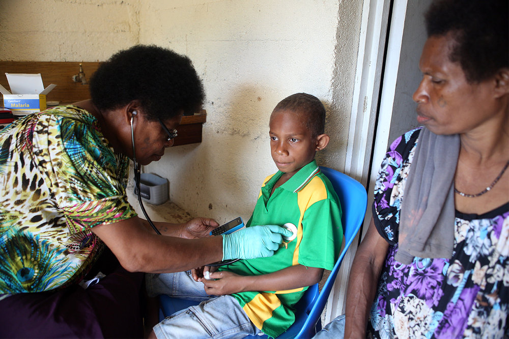 Nursing Officer Mother Mary Salib examines Samson for malaria, while his mother, Bernadette, looks on. St Martin de Porres Health Centre in Mugil, Madang Province, Papua New Guinea.