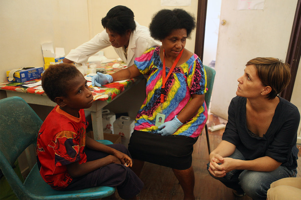 Dr Leanne Robinson looks on as Jonathan, 9, gets tested for malaria by Nursing Officer Kay Kose and microscopist Barbara Sambre after presenting at Madang Town Clinic with symptoms. Madang, Papua New Guinea.