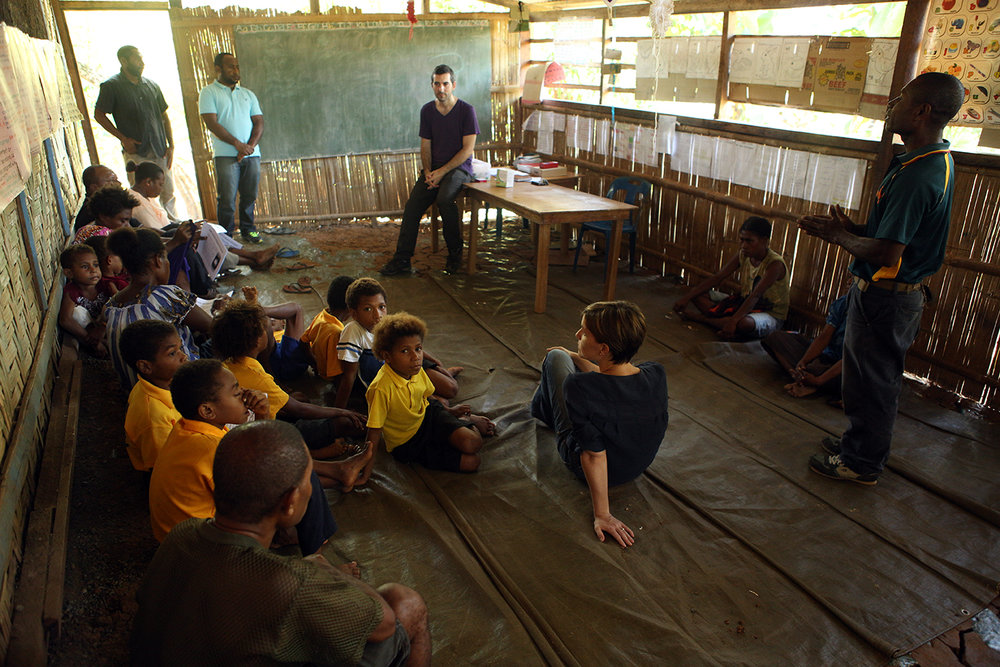 Dr Leanne Robinson listens, while Dr Cyrille Czeher, accompanied by Scientific Officer Lincoln Timinao and Nursing Officer David Teine, update students and parents on an ongoing malaria study at Houdini village school near Madang, Papua New Guinea.