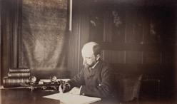 Henry Adams seated at desk in dark coat, writing. Photograph by Marian Hooper Adams, 1883.
