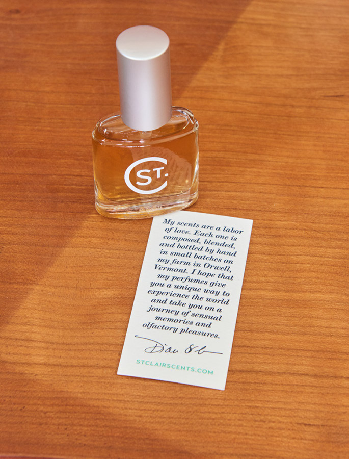 St. Clair Scents perfume bottle on desk with note card