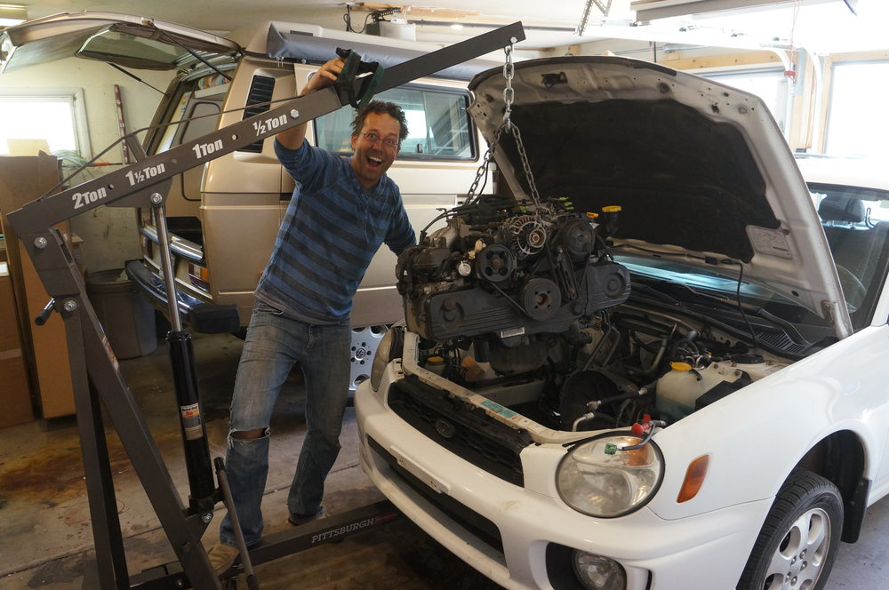 "April 2017 - Chip, a.k.a. ""The Mad Scientist,"" pulling out the Impreza engine so Spud can soon keep up with other cars on the road.  Don't let him anywhere near your Subaru.  Note the headlamp-induced hair style which is vaguely reminiscent of the sweet bowl-cut he sported in high school.  Try not to be jealous."