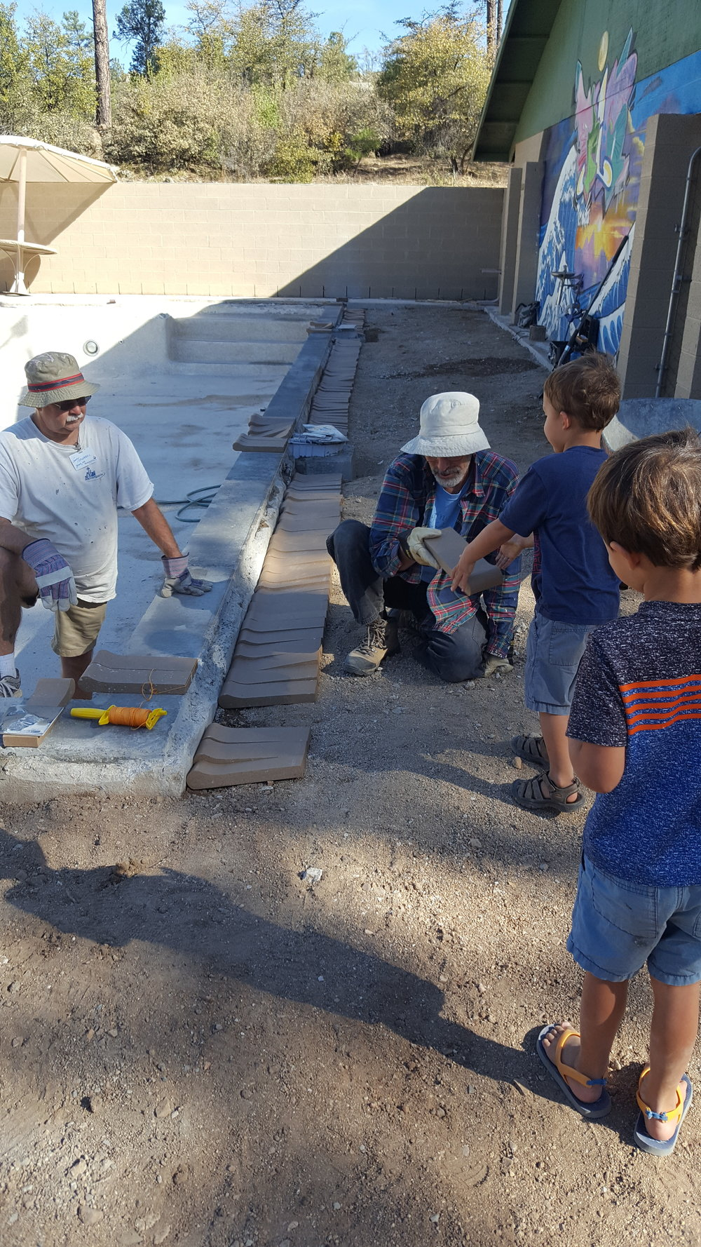 Helping the guys lay the bricks for the pool.