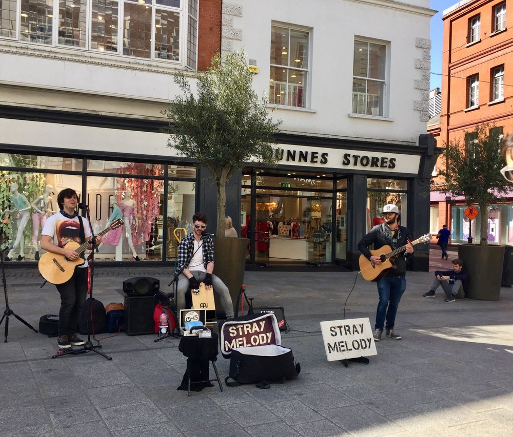 A beautiful mix of storefronts, restaurants, and music performers line Grafton Street