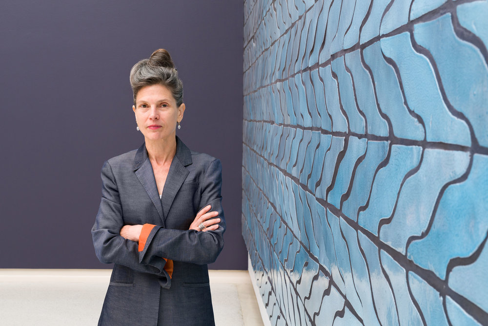 Ingrid Schaffner, curator of the 57th  Carnegie International  in front of Sarah Crowner's  Wall (Wavy Arrow Terracotta) , 2018.   © Carnegie Museum of Art, Pittsburgh. Photo: Bryan Conley.