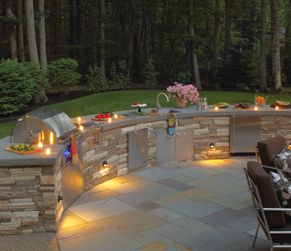 Top landscape design with an outdoor kitchen and lighting inWaltham, MA