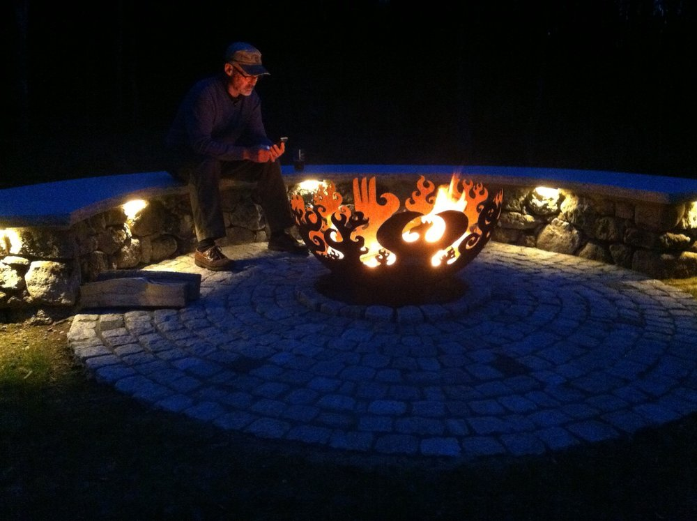 Beautiful landscape design with an outdoor fireplace area in Milford, NH