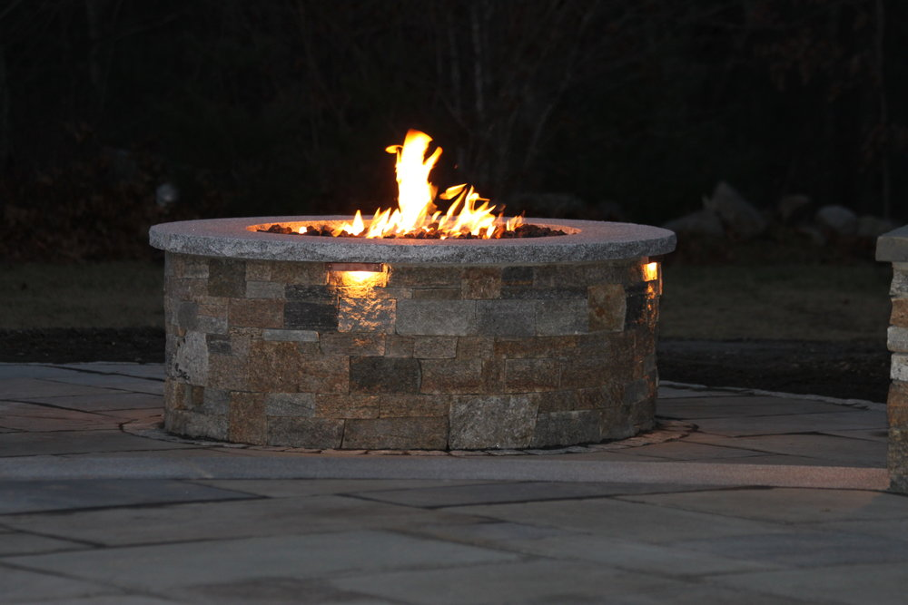 Top landscape design with an outdoor fireplace in Waltham, MA.
