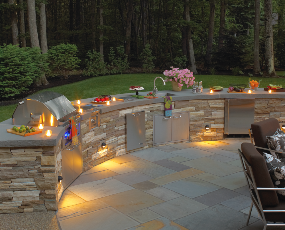 Professional landscape design with stone veneer outdoor kitchen in Laconia, NH