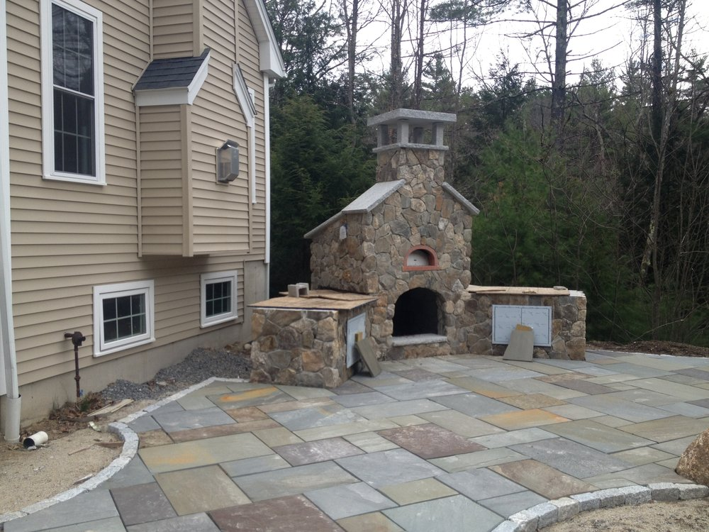 Professional landscape design with an outdoor fireplace in Waltham, MA.