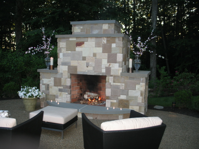 Beautiful landscape design with an outdoor fireplace area in Waltham, MA.