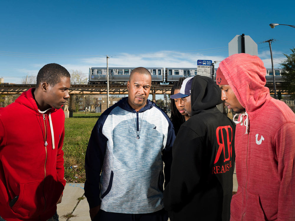 "Gun violence ""interrupter"" Cobe Williams pictured in the Washington Park neighborhood of Chicago's South Side with men whom he mentors. For People magazine Nov 2015."