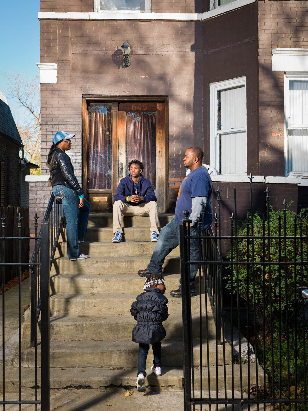 Cure Violence program coordinator Joshua Brooks speaks with Orr Academy high school student Jeryon Stevens (center,) his sister Jaziyah Vaughn and their mother Chrishona Hodges outside their Garfield Park home.