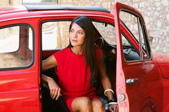 mujer en vestido rojo saliendo de un coche rojo