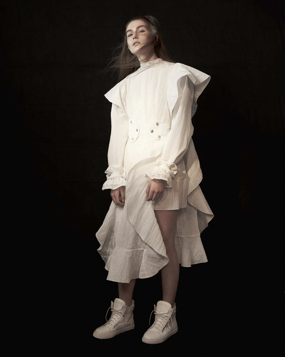 White textured nylon top worn under apron dress with removable belt from A.W.A.K.E. White cotton cuffs from Renli Su White sneakers from Fengchen Wang
