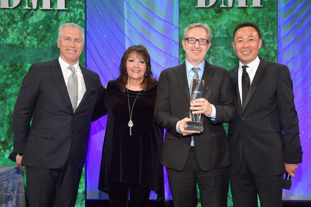 Rick Baitz  accepts award BMI Classic Contribution Award from BMI Vice President, Creative - Film, TV & Visual Media  Doreen Ringer Ross , Executive Vice President of Creative & Licensing at BMI  Mike Steinberg  and BMI Assistant Vice President of Creative, Los Angeles  Ray Yee