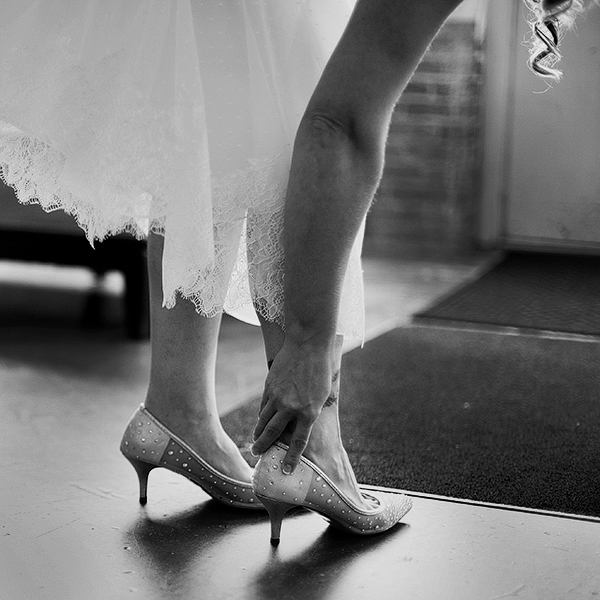 Bride putting on shoes photography