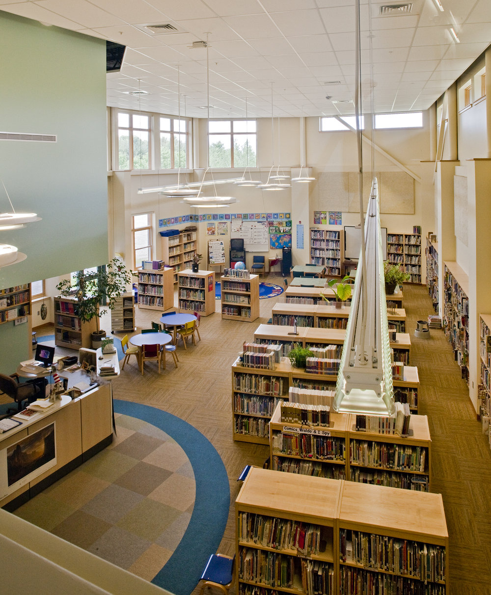 A two-story library captures daylight and can be viewed from multiple angles from surrounding spaces.