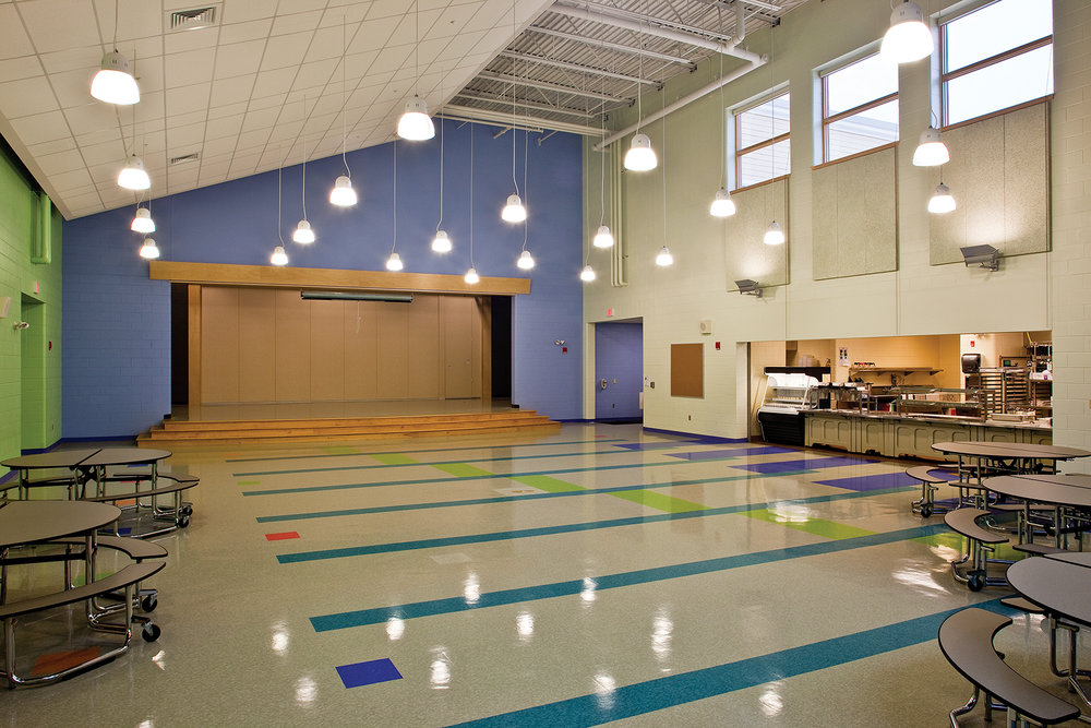 This flexible space combines cafeteria, kitchen, and stage functions. The back of the stage opens to the gym, so the school can host multiple events at once.