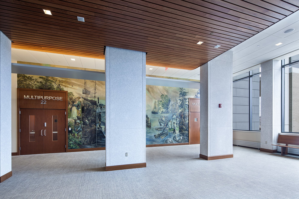 "Public spaces were designed to maximize views of the Kennebec River, visible through the windows on the right. Painter Christopher Cart immortalized members of the design team and the judiciary in the faces of steamboat passengers in one panel of his ""Kennebec"" mural."