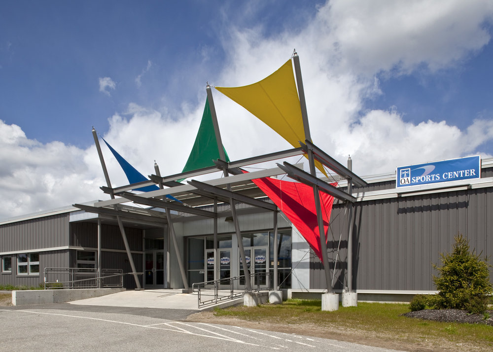 Colorful banners on a steel canopy mark the entrance to an otherwise gray and featureless building.