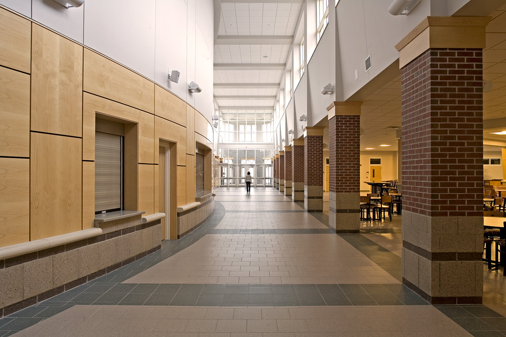 A daylit main street connects the entry to the food court, administrative offices, student services, the auditorium, and the gym.