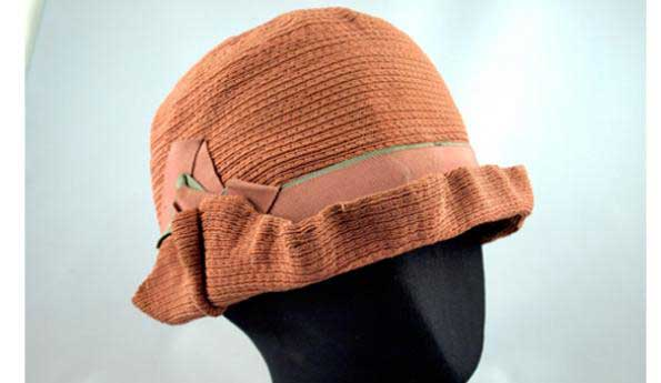 Cloche Hat    Significance:     This hat was made in the small millinery shop of Lily Evans, which was established in Vancouver in 1923.  In the early part of the 20th century, millinery was a feasible way for a woman to make a living, requiring little capital or specific training. Milliners could re-trim last season's hat, as well as sell this season's model.  This hat was purchased in Vancouver by Mrs. D. McCaffrey, the wife of Dr. Peter McCaffrey of Aggassiz.   Date Range:  c. 1923 - 1935   Place of Manufacture:  Made by Lily Evans Millinery, Vancouver   Dimensions:  15.5 cm high, 19 cm diameter   Museum Location:  Storage   Catalog Number:  H993.39.7   Donor:  S. and Rory Wallace